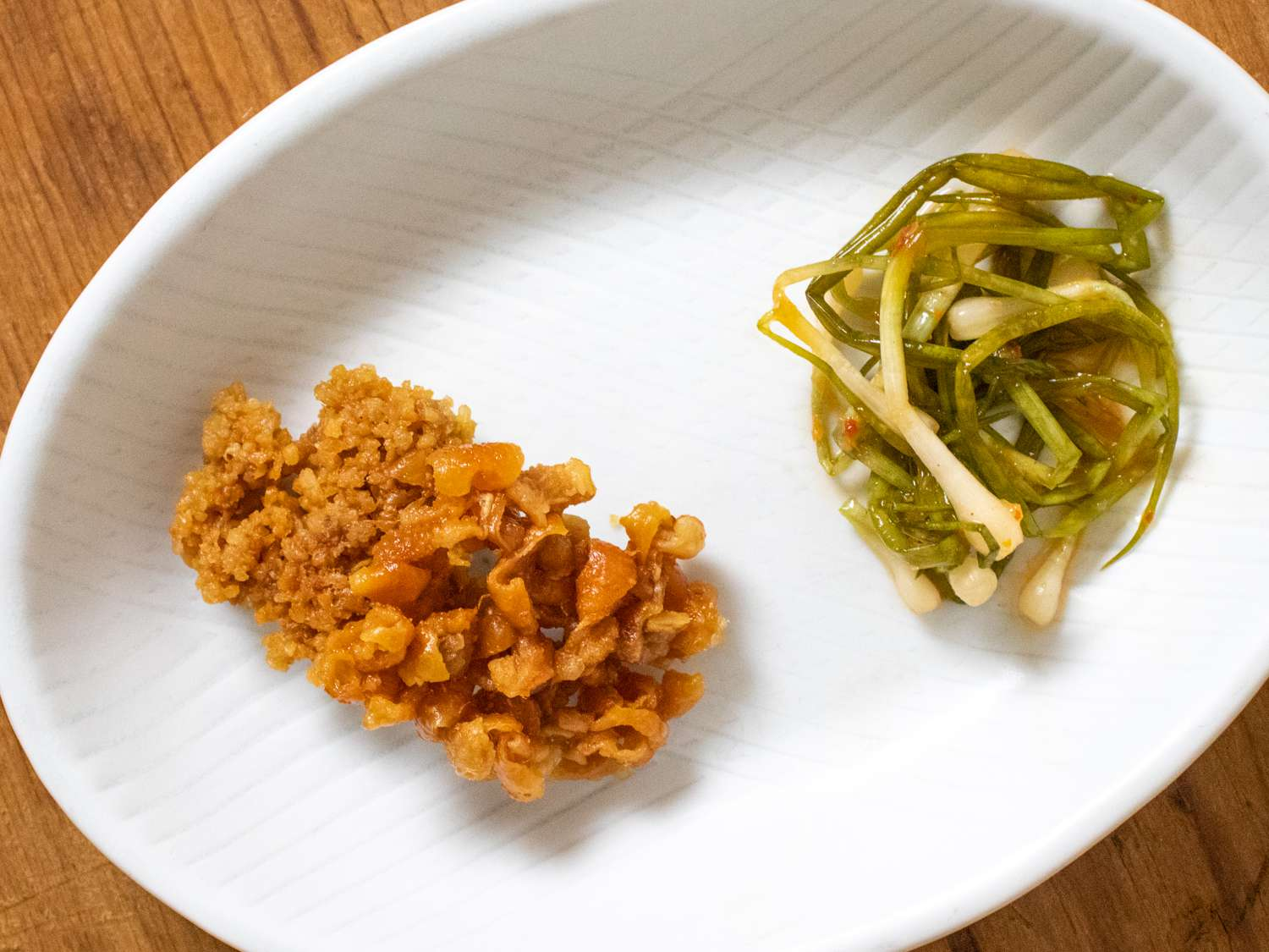 Little chicken skin chips on a plate with a pile of naga negi kimchi
