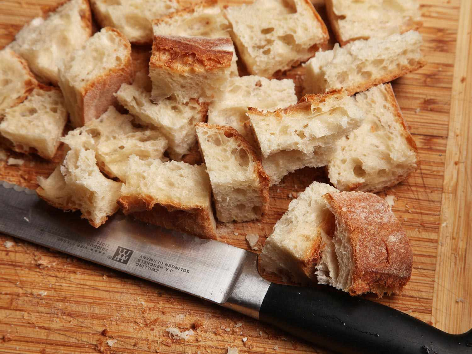 Cubed crusty bread on a wooden cutting board, next to a knife