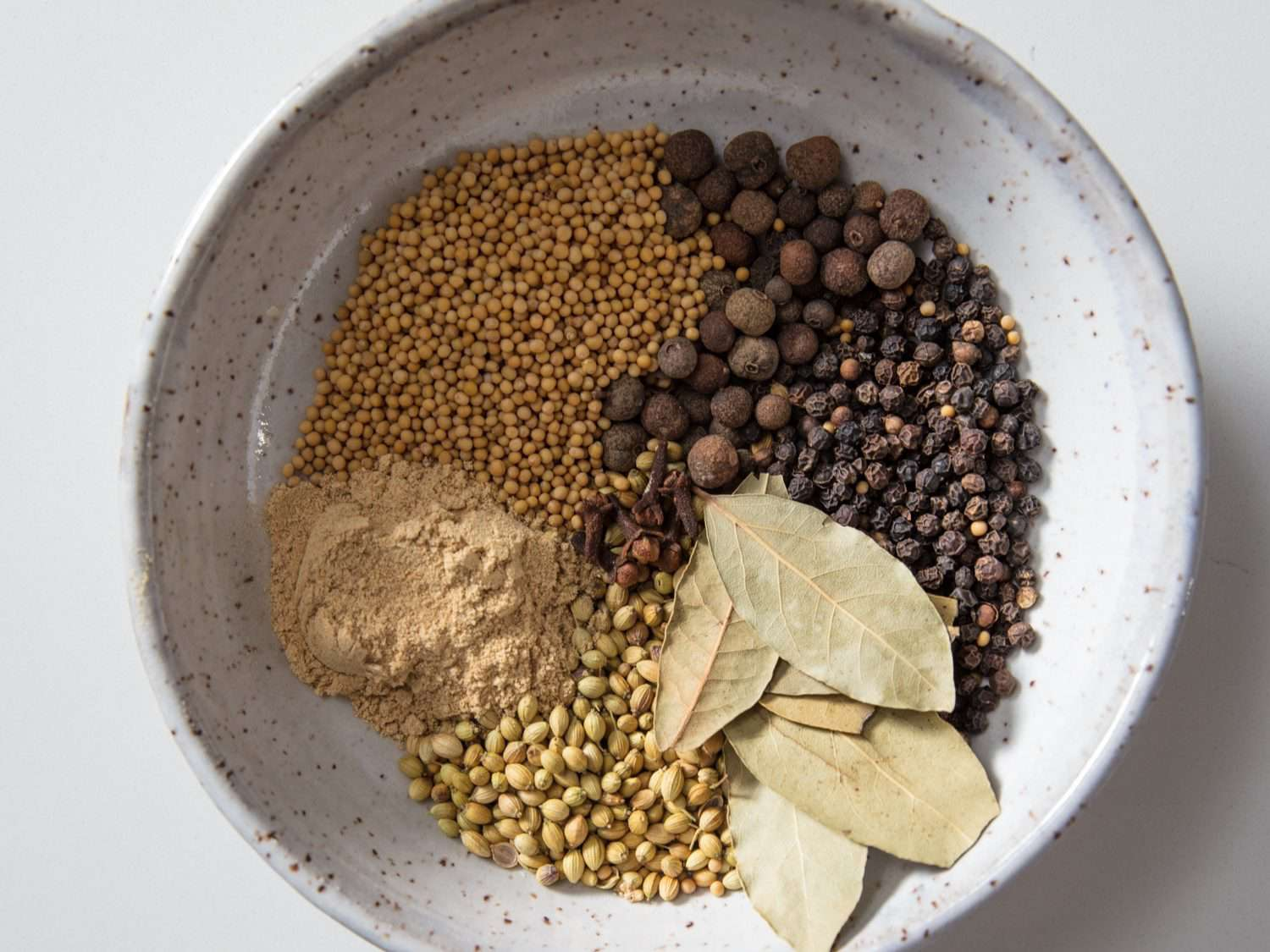 A bowl with ingredients for corned beef rub: mustard seed, allspice, black peppercorns, bay leaves, coriander, and ground ginger.