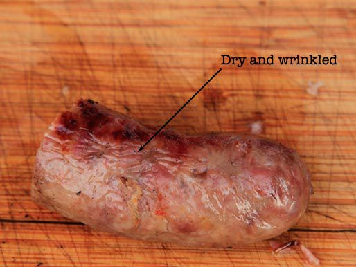 Half a cooked sausage, with a label pointing out its dry and wrinkled exterior