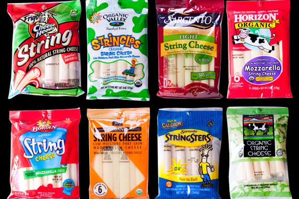 An assortment of eight different packages of string cheese.