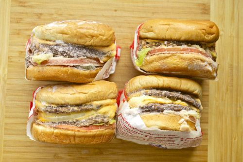 Four frozen In-N-Out burgers with wrappers