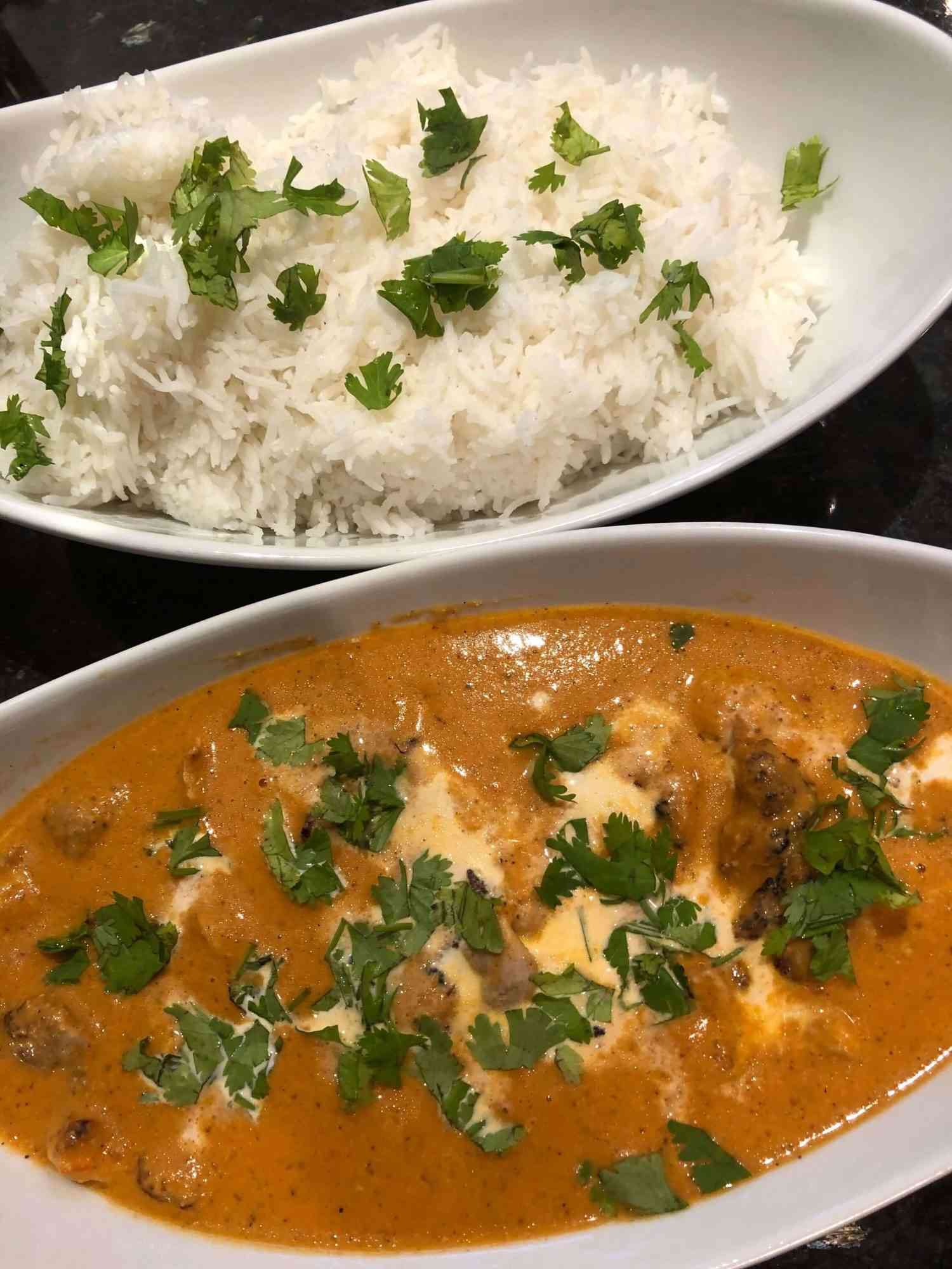 butter chicken in a serving bowl with rice alongside