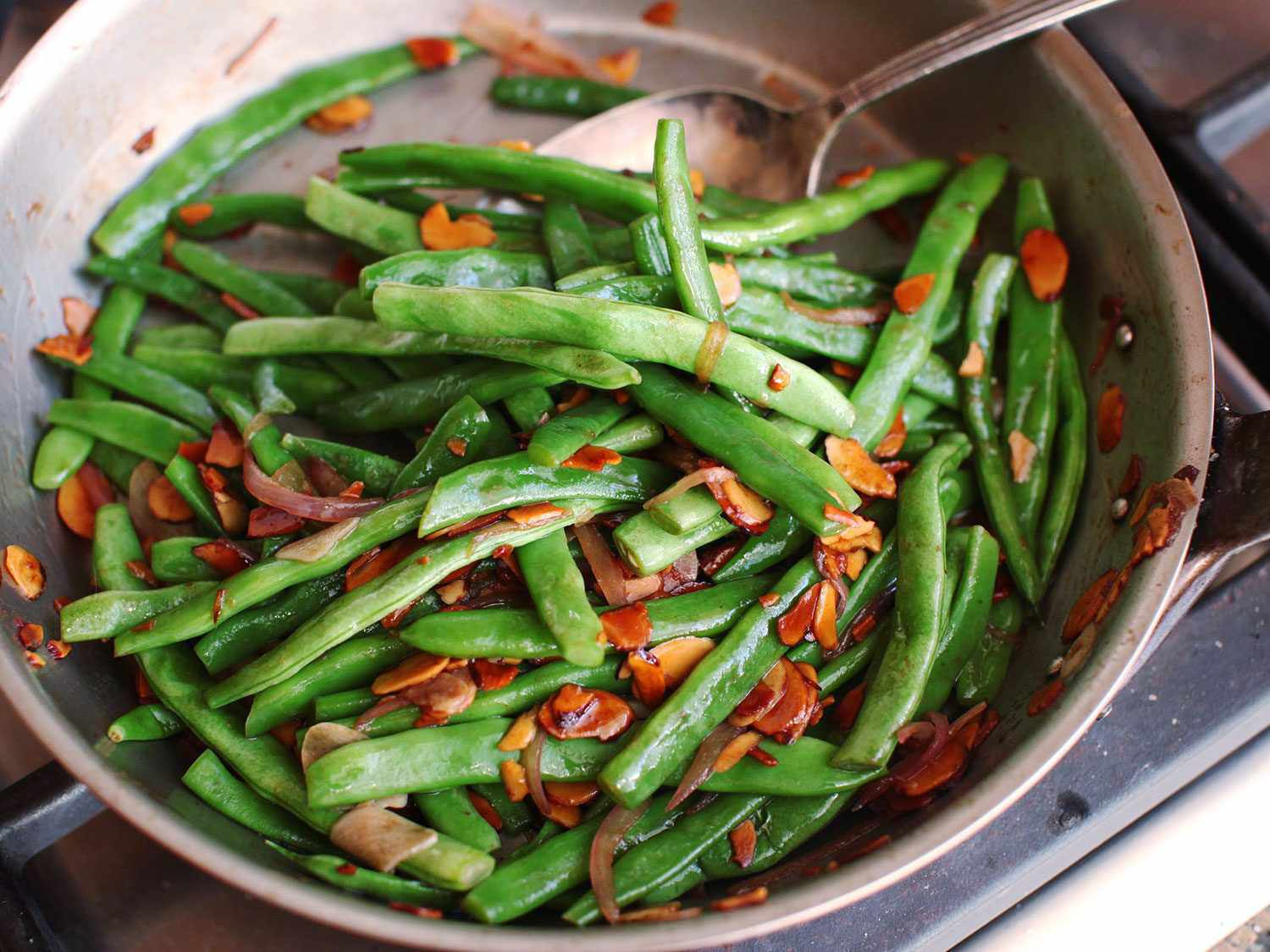 Closeup of green beans Amandine in a skillet.