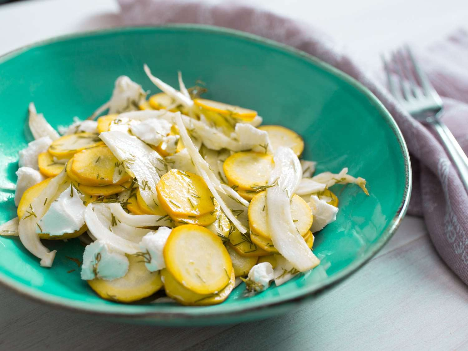 A ceramic dish of Summer Squash Salad With Goat Cheese, Fennel, and Dill