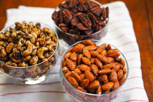 Three glass dishes of spiced nuts on a kitchen towel on a table. The flavors are smoky candied almonds, Mexican spiced chocolate pecans, and olive-rosemary cashews.