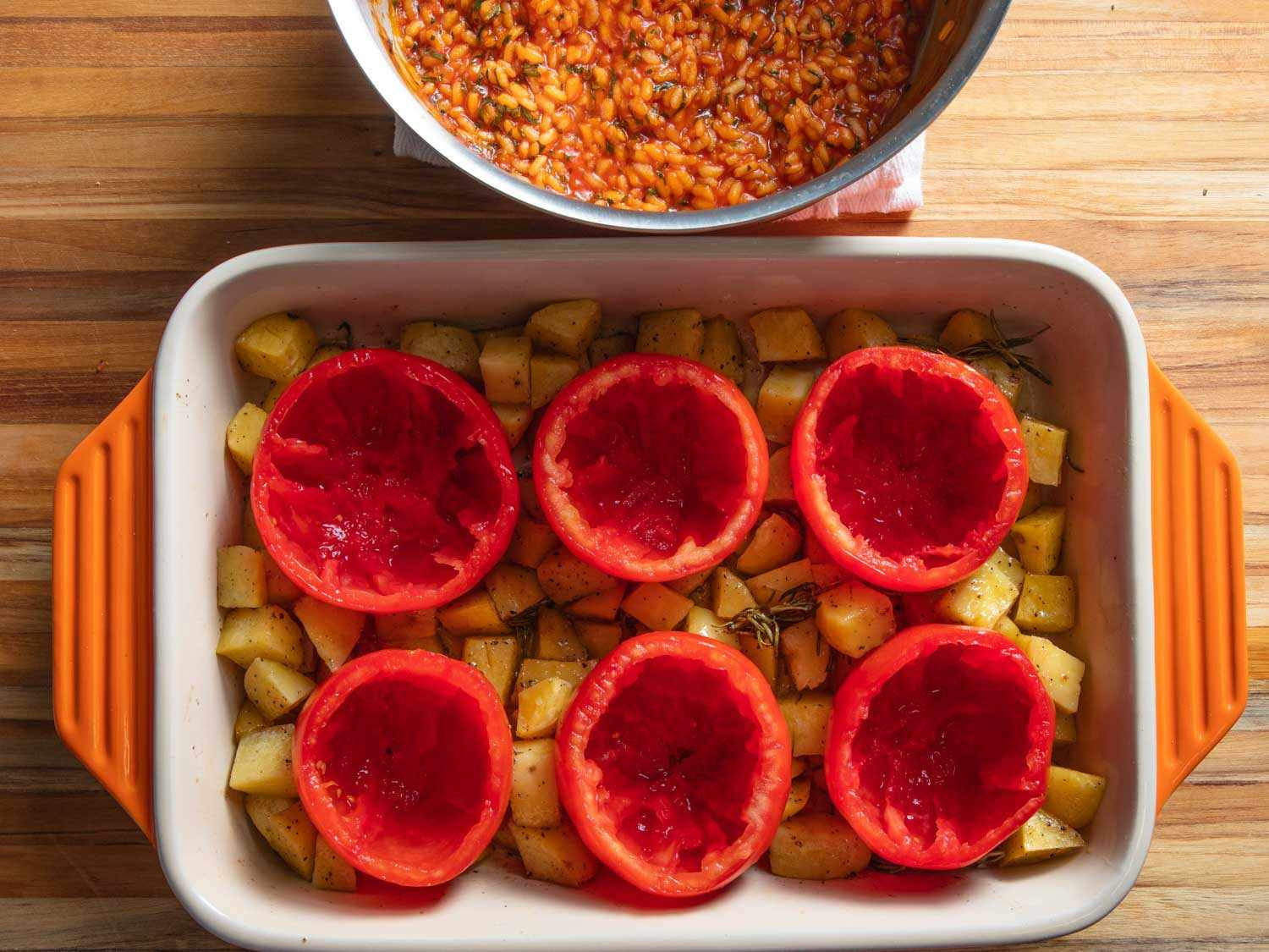 Overhead of hollowed-out tomatoes nestled in a baking dish with potatoes.