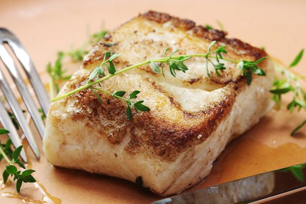 Butter-based sous vide and seared halibut with a sprig of thyme on top.