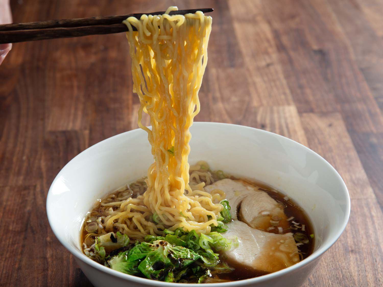 Noodles being lifted out of bowl of turkey ramen