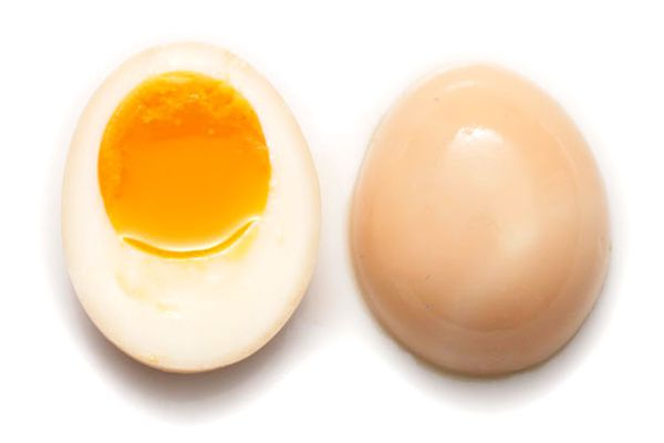 A marinated soft boiled egg (ajitsuke tamago) for ramen, sliced in half to show marinated exterior and soft yolk.