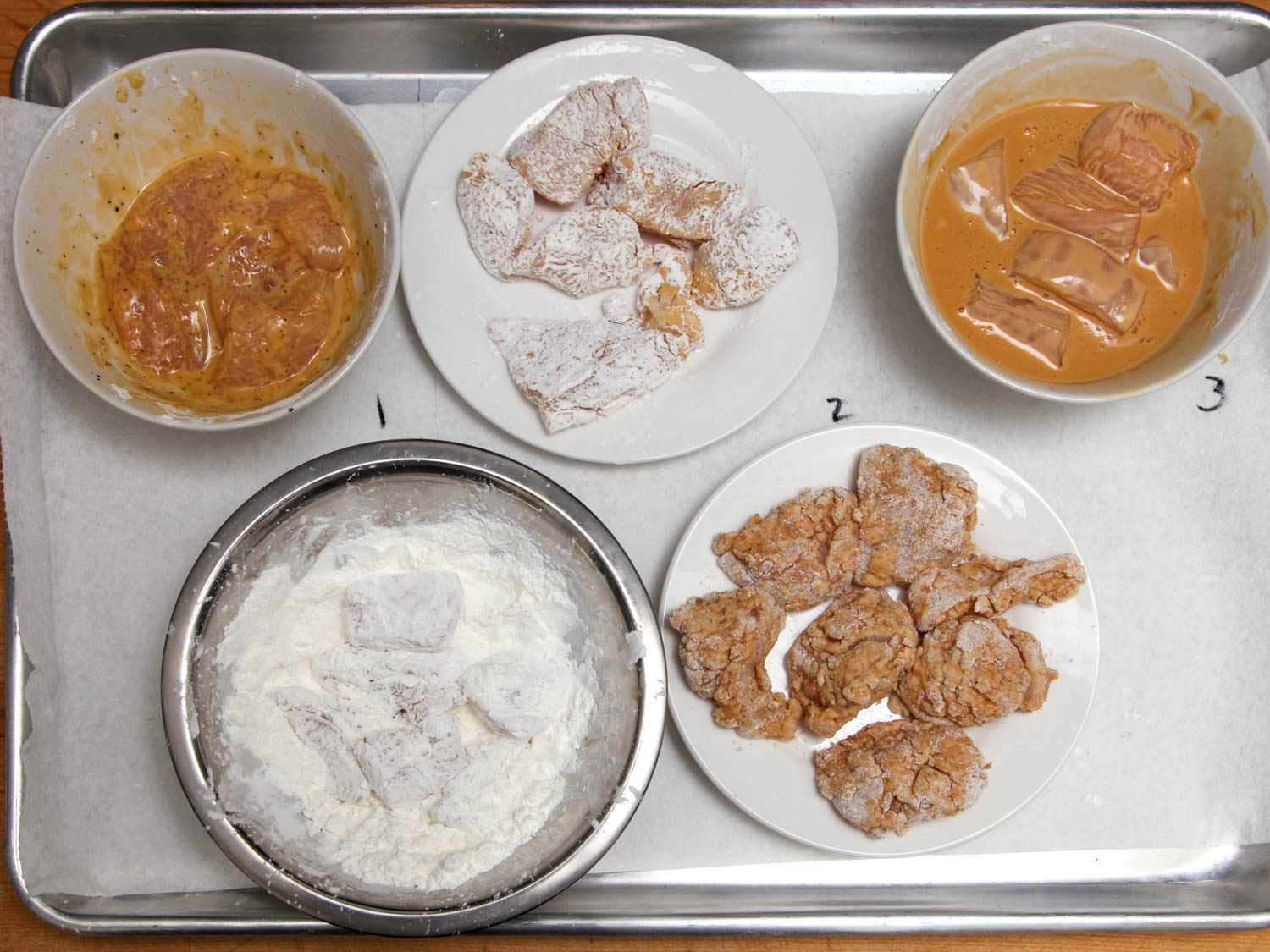 Boneless chicken thighs cut into pieces and in five different bowls with five different breadings or batters.