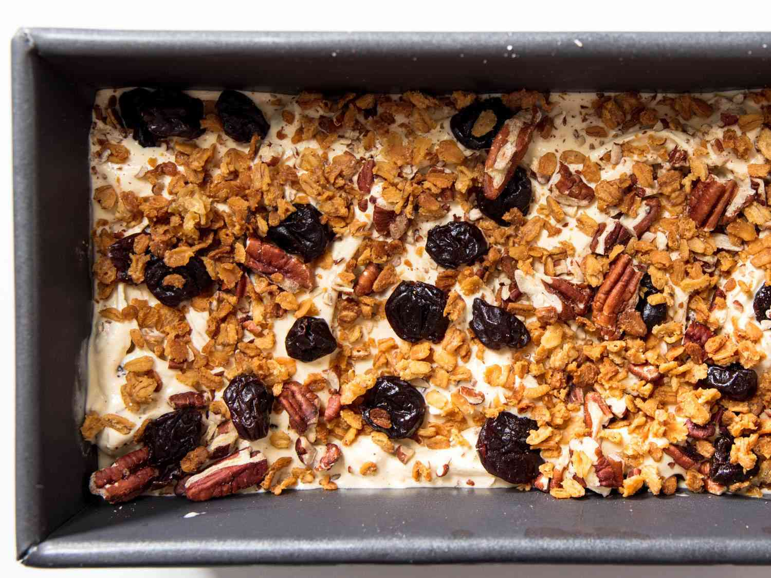 Loaf pan filled with oatmeal cookie ice cream, covered in dried fruit, nuts, and oat clusters