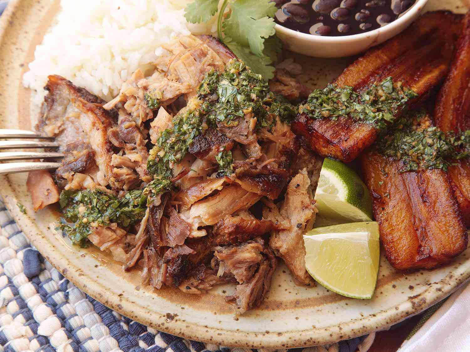 Sliced Cuban roast pork on a ceramic plate with white rice, mojo, black beans, and fried plantains