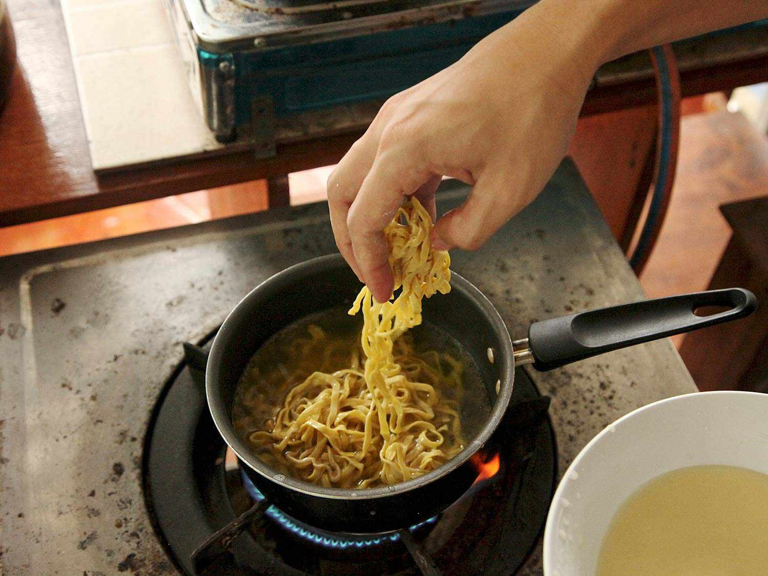 Boiling noodles in water for Khao Soi Gai.