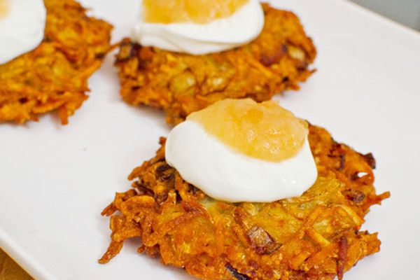 Latkes on a platter topped with sour cream and applesauce.