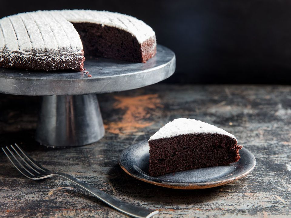 A slice of chocolate olive oil cake on a plate, next to the full cake on a cake stand