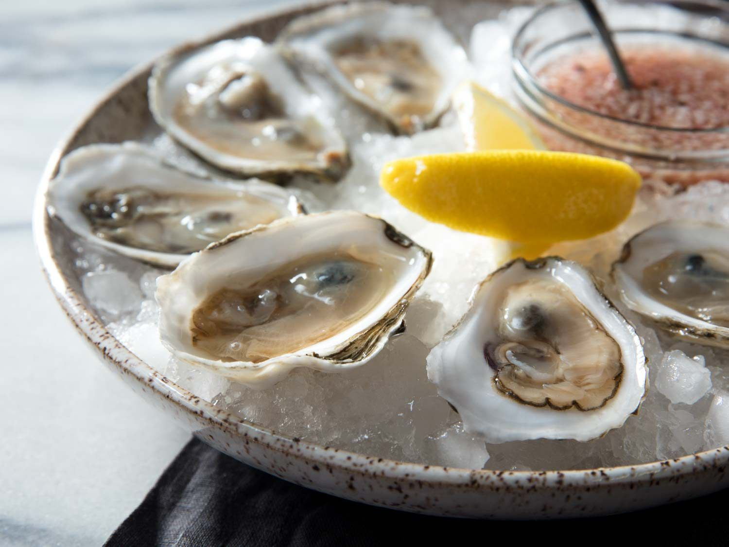 Side view of bowl of oysters with mignonette and lemon wedges