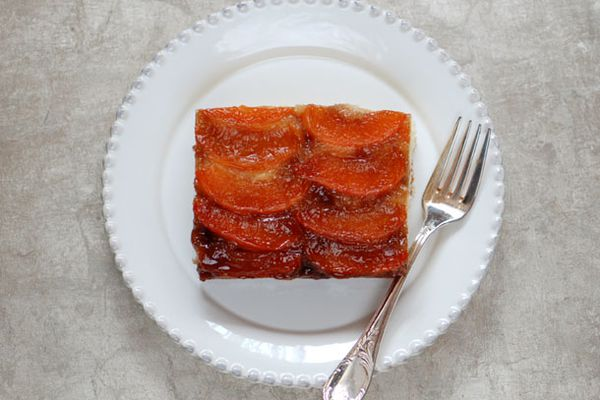 Square slice of apricot turnover cake on a white plate with a fork on the side.