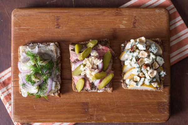 Three different Smørrebrød on a wood cutting board, each with different toppings.