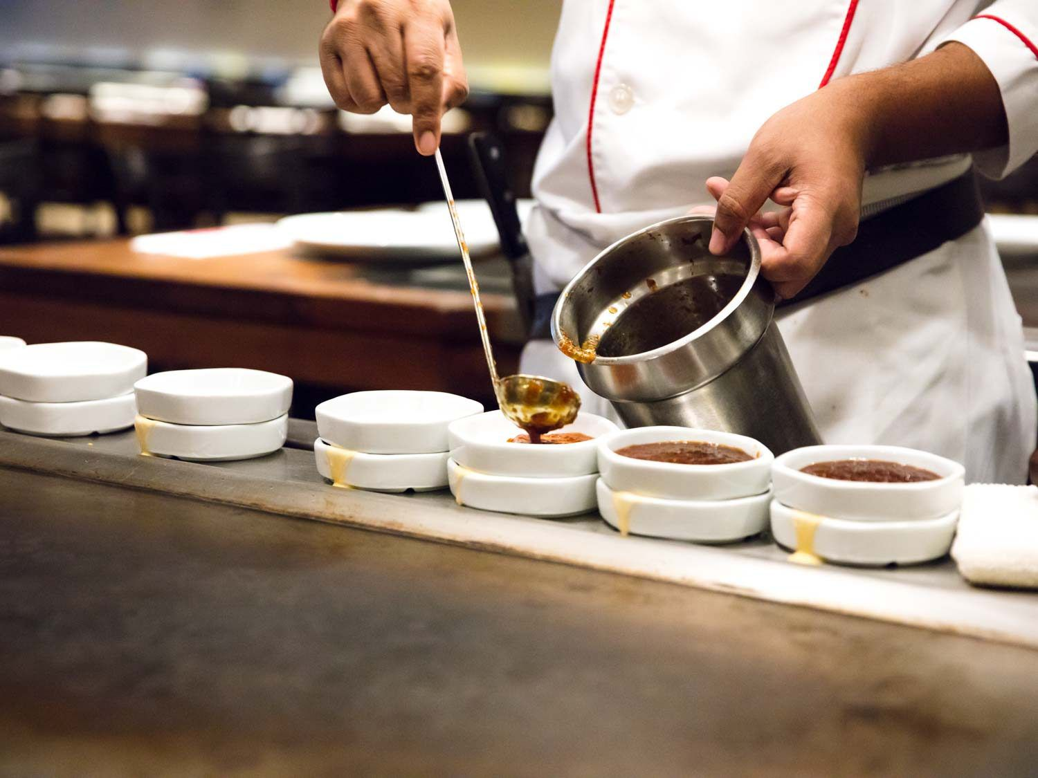 A Benihana cook portioning out dipping sauces