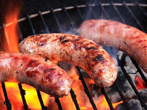 Sausages cooking on a charcoal grill