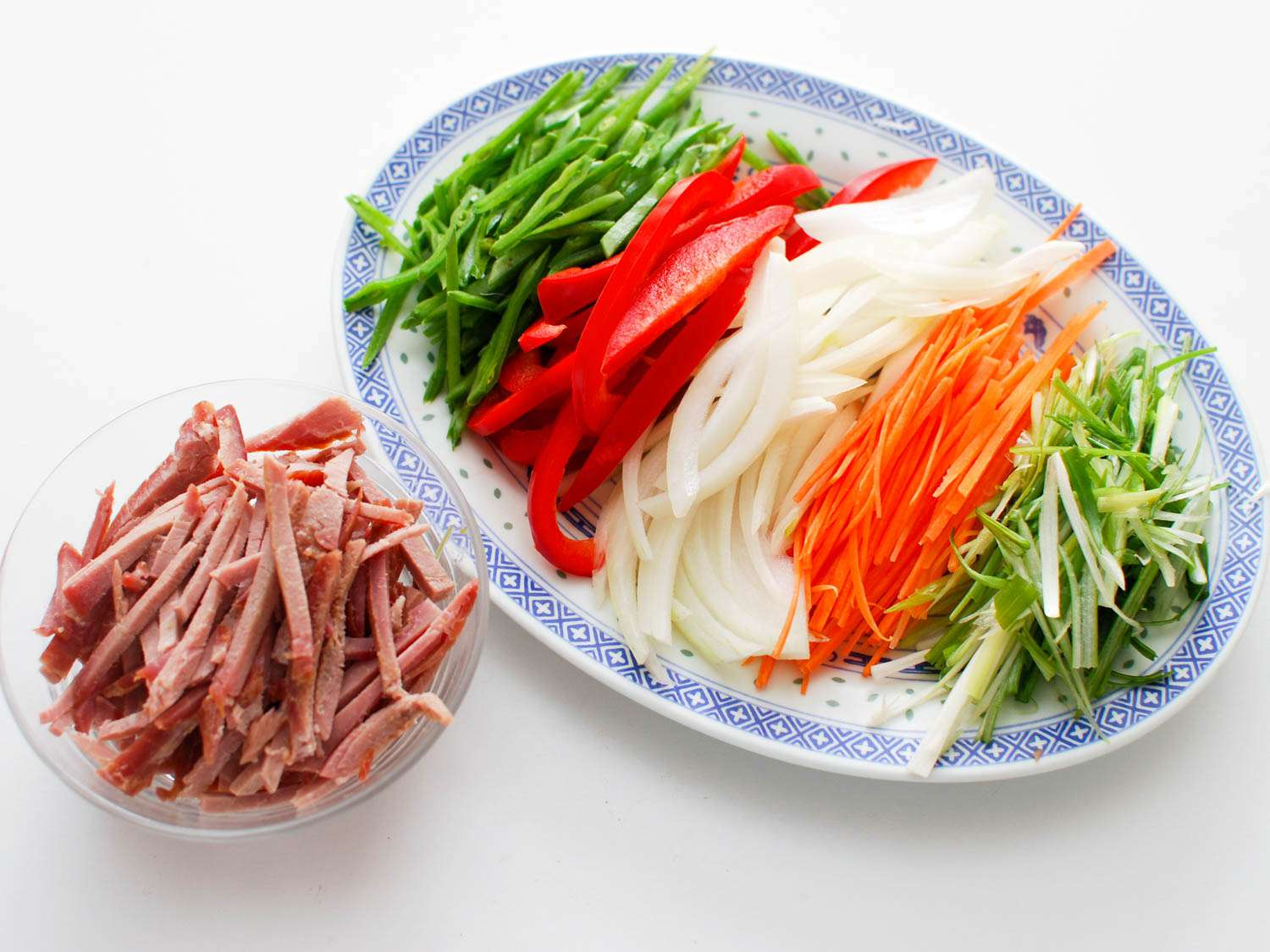 Thin sliced snow peas, red bell peppers, onion, carrot, and scallions in a platter next to a small bowl of char siu.