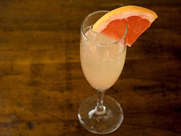 A grapefruit and ginger sparkler in a Champagne glass with a wedge of grapefruit on the rim.