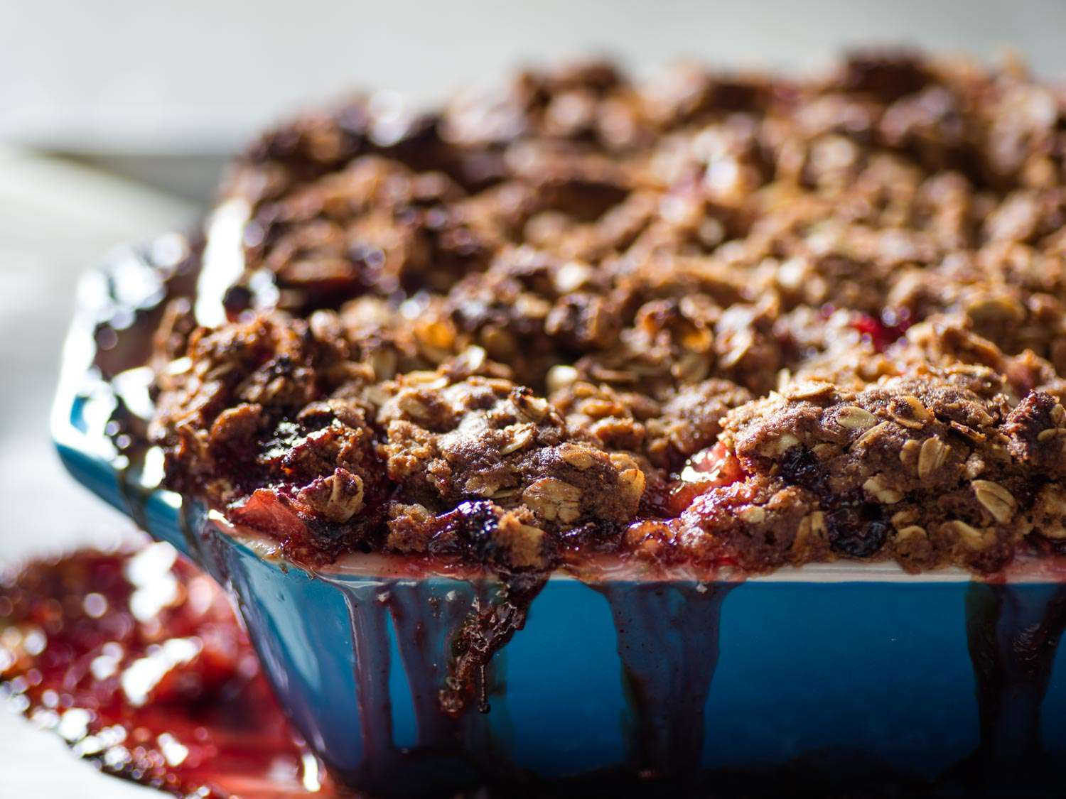 Close-up of a blue ceramic baking dish of strawberry-rhubarb crisp, with fruit filling spilling over the side