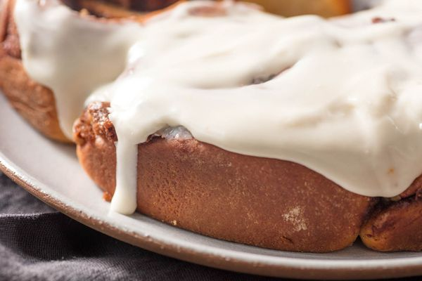 Close-up of overnight cinnamon rolls topped with cream cheese frosting.