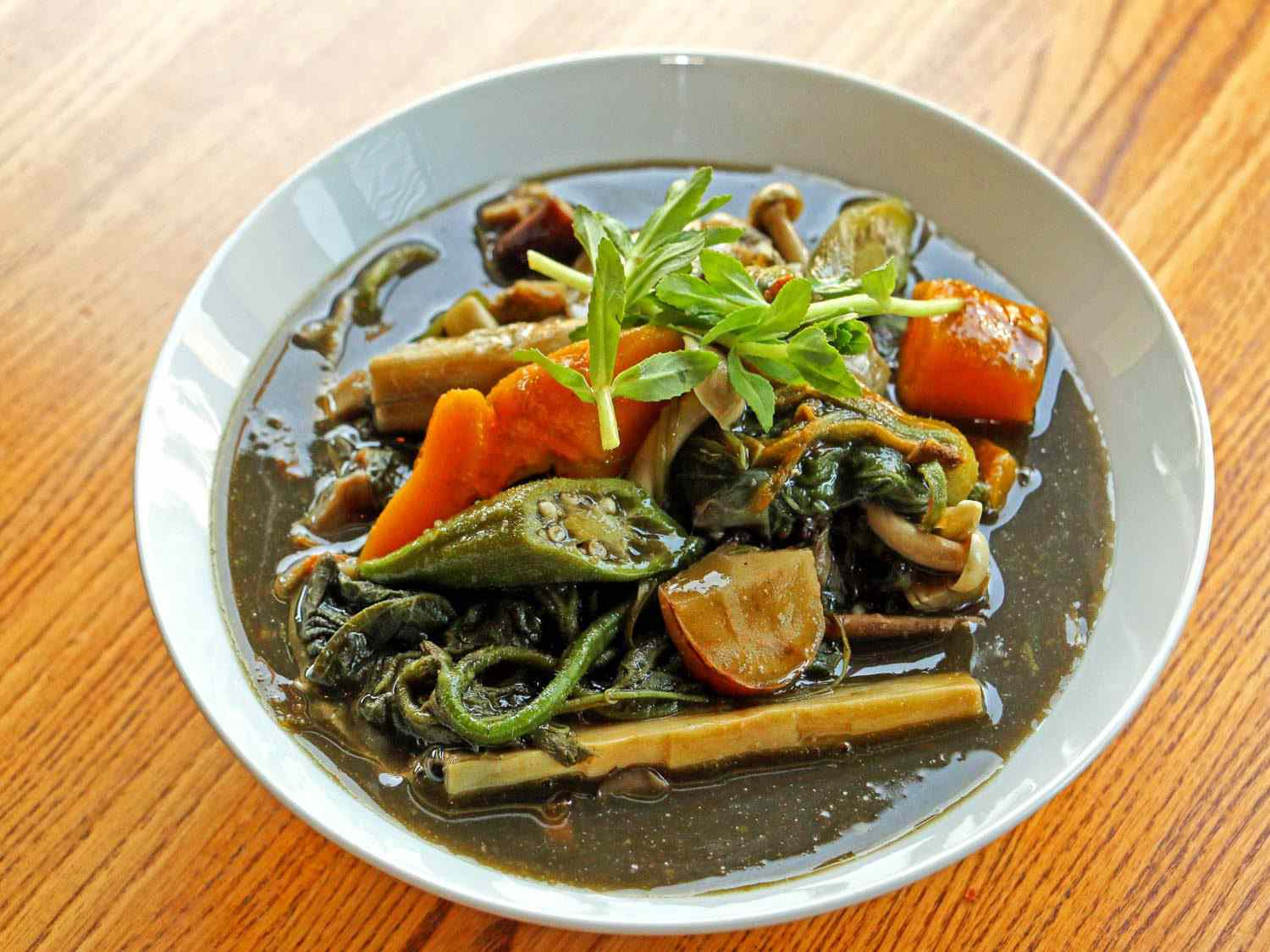 A bowl of gaeng naw mai: a dark-green broth with bamboo shoots, green yanang leaves, and other vegetables and herbs