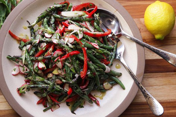 Green beans with peppers and radishes on a stone plate sitting on a wooden cutting board.