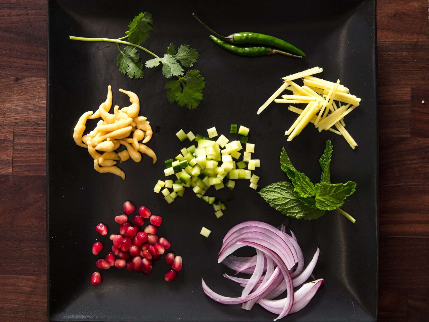 red onion, boondi, herbs, Thai green chilies, pomegranate seeds, diced cucumber