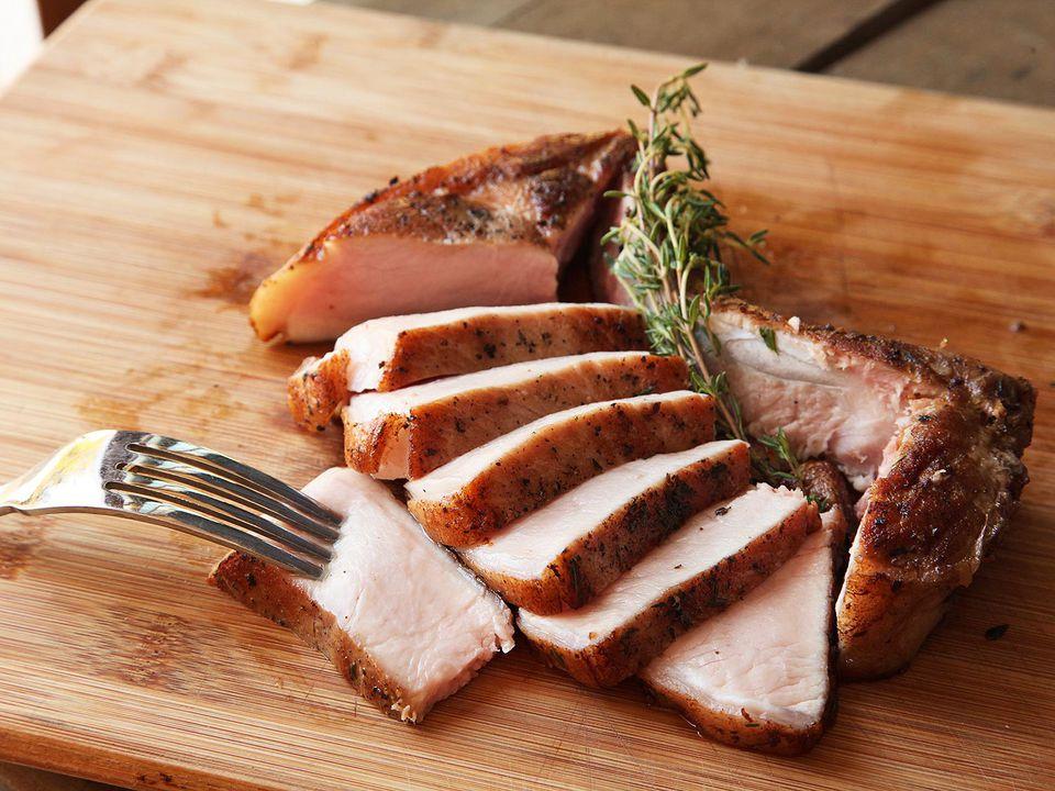 Sous vide bone-in pork chop, sliced, on a cutting board.