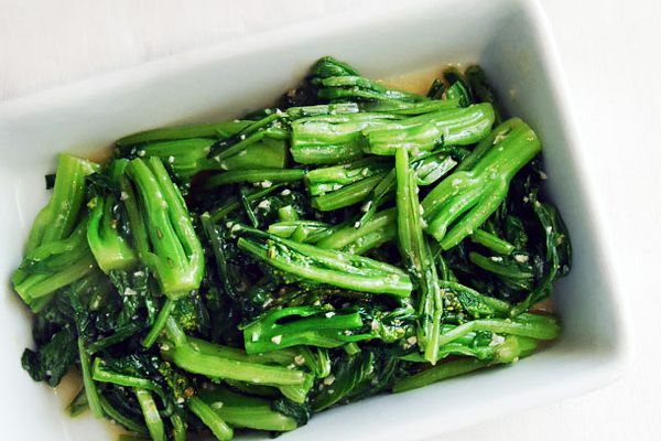 Stir-fried choy sum with minced garlic in a white rectangular serving dish.