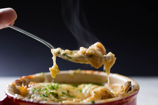 Spoon pulling out a bite of cheese-topped French onion soup from red bowl.