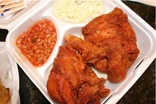 Hot fried chicken in a styrofoam takeout container with coleslaw and baked beans on the side.