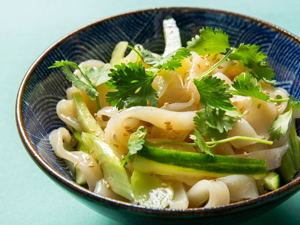Bowl of cold sesame noodles topped with cucumber, celery, and cilantro