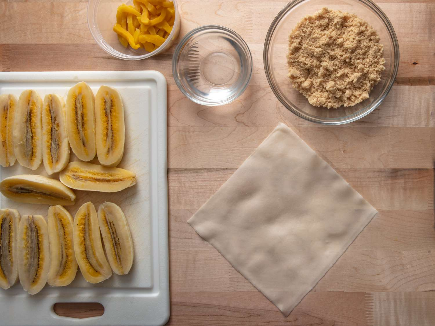 a workstation for making turon: saba bananas, brown sugar, jackfruit, a bowl of water, and a spring roll wrapper