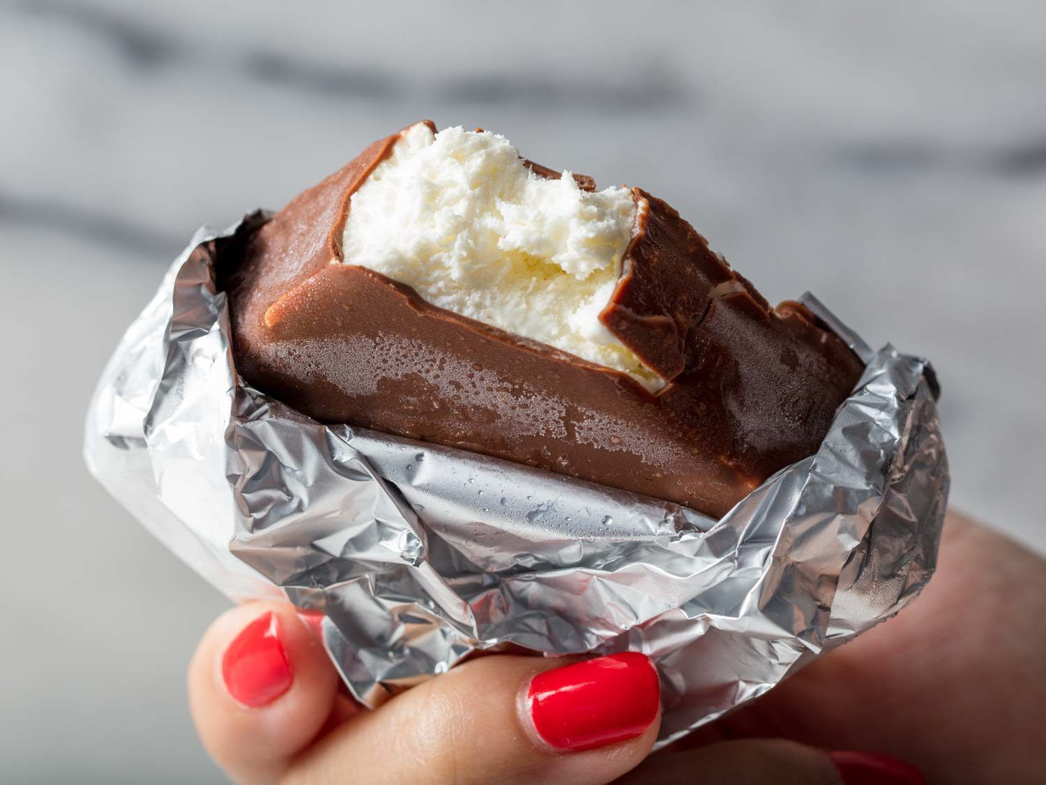 A hand holding a foil-wrapped homemade Klondike ice cream bar with a bite taken out