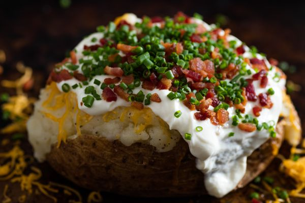 A loaded baked potato with cheese, sour cream, bacon crumbles, and chives.