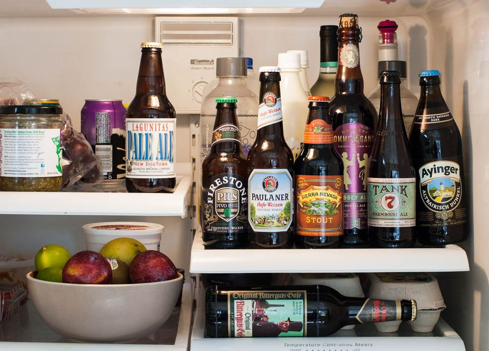 Seven different bottles of beer in a refrigerator. Six are all on one shelf with the labels facing out.
