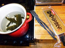 Dried kelp soaking in a pot of water with a package of dried kelp on the counter next to the cooktop.