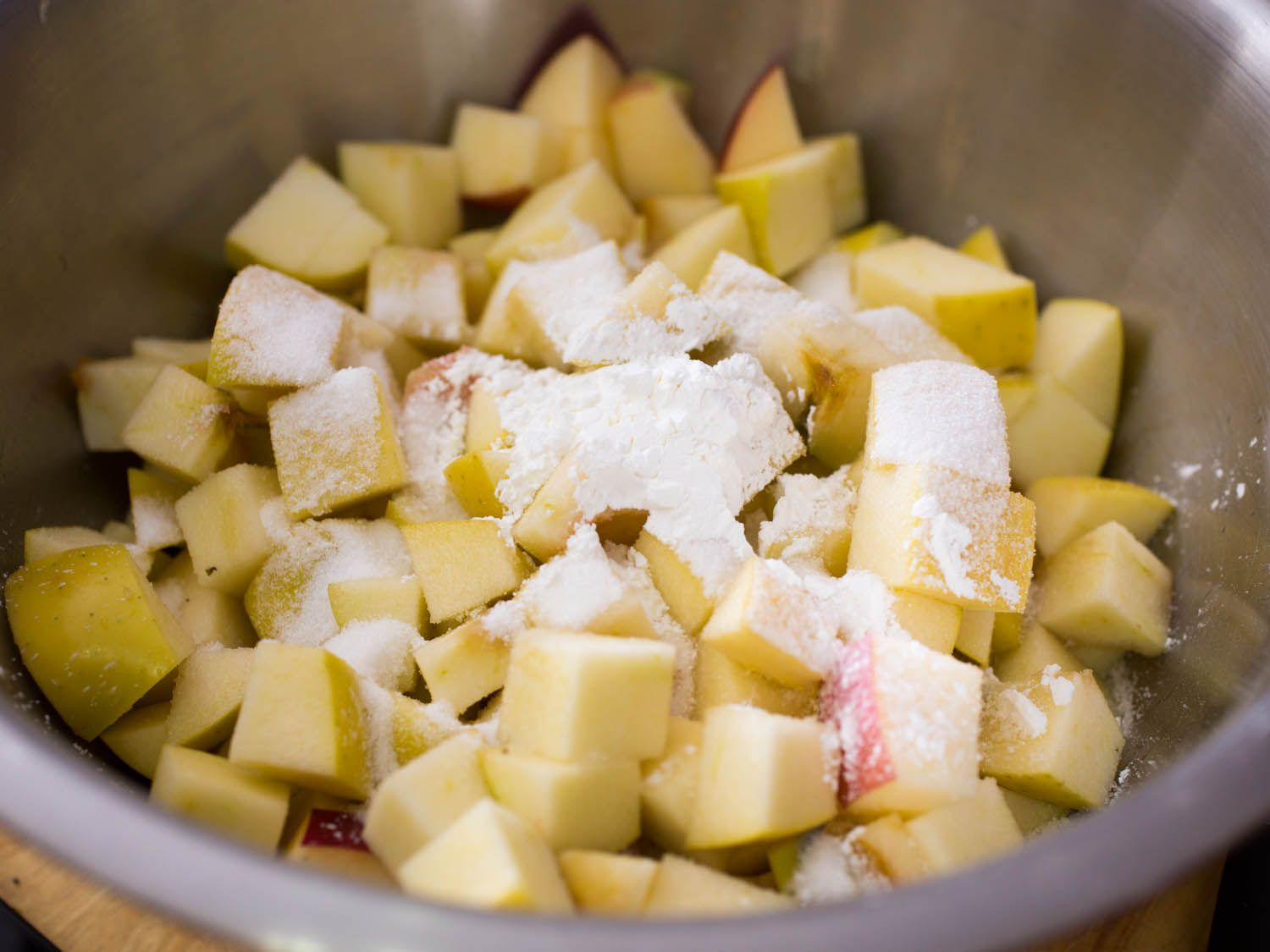 Chopped apple in a metal bowl with cornstarch and sugar sprinkled on top
