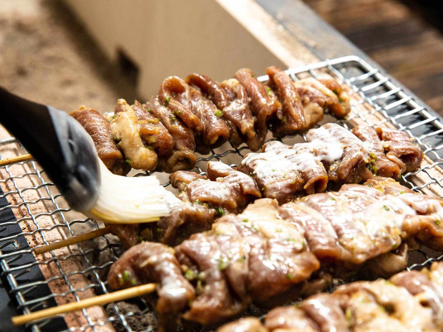 Closeup of Thai pork skewers being brushed with a pastry brush while resting on a wire mesh rack, suspended over coals