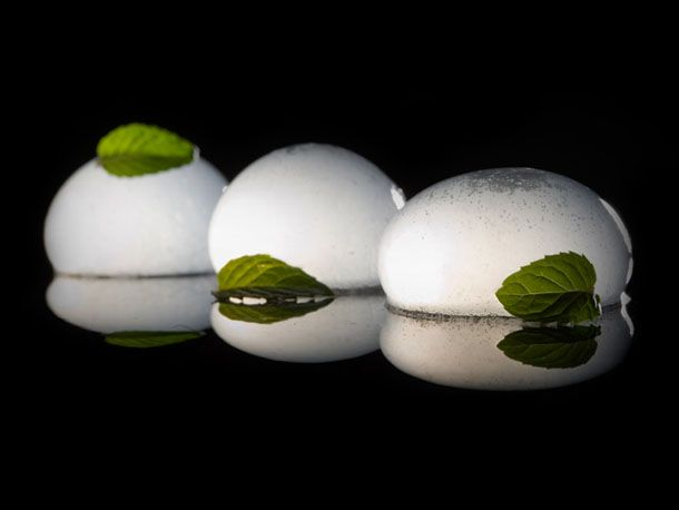 Carbonated mojito spheres garnished with mint leaves.