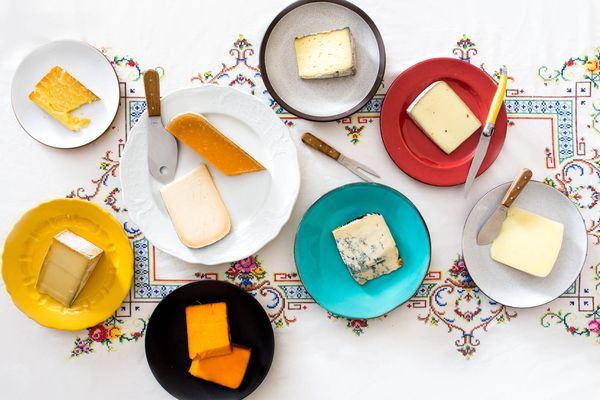 An assortment of cheeses, each on a separate plate with cheese knives.
