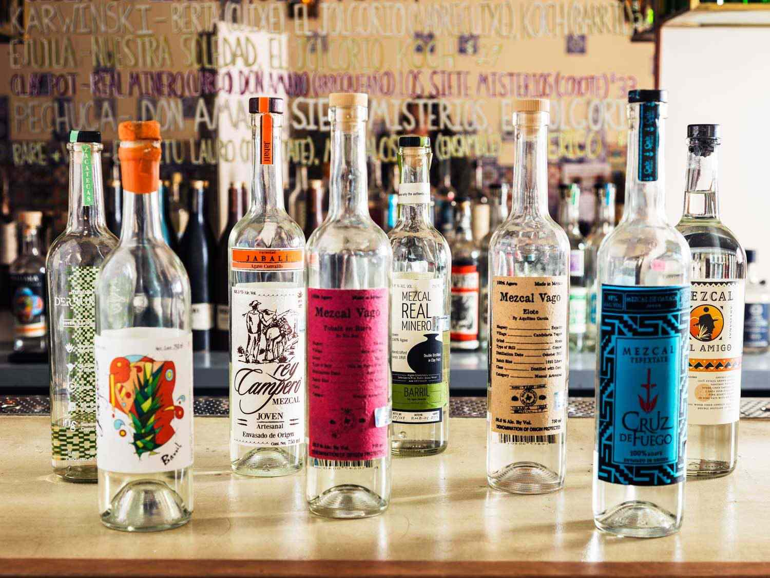 A selection of tequilas in bottles on a bar counter at Madre Mezcaleria.