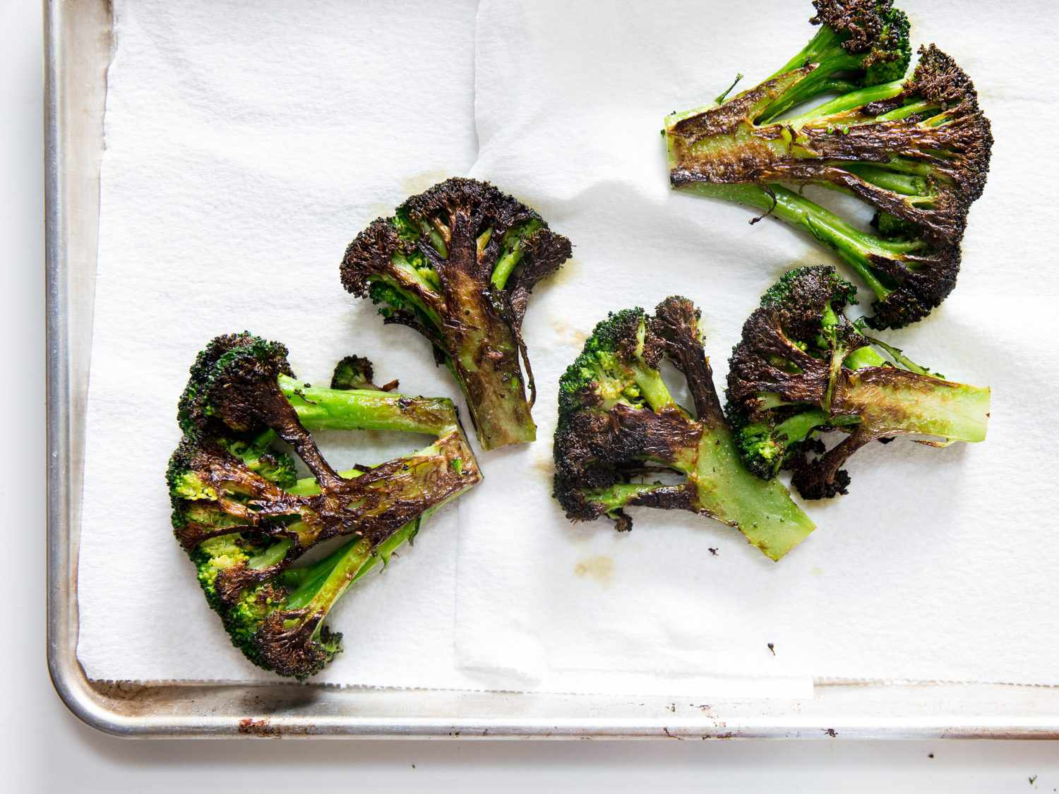 Charred broccoli pieces on a paper towel–lined baking sheet.