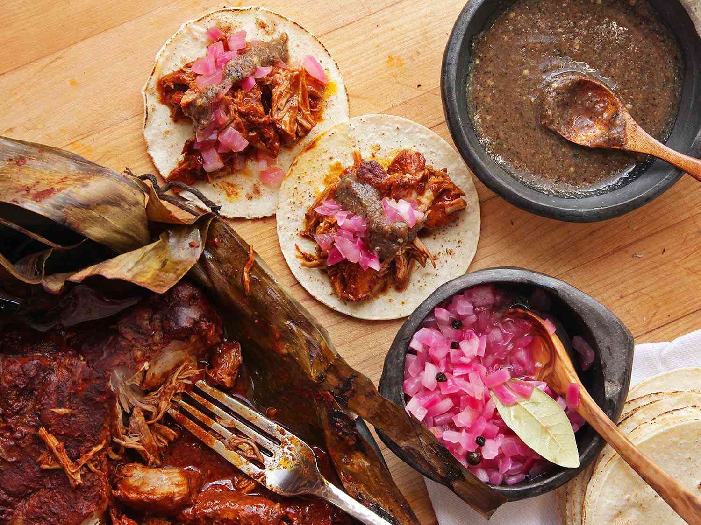 Serving finished cochinita pibil pork on tortillas.