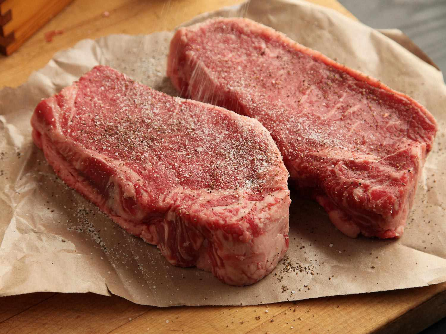 Two thick steaks seasoned with salt and pepper